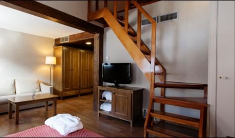 Habitación duplex. Escalera de madera para acceso piso superior